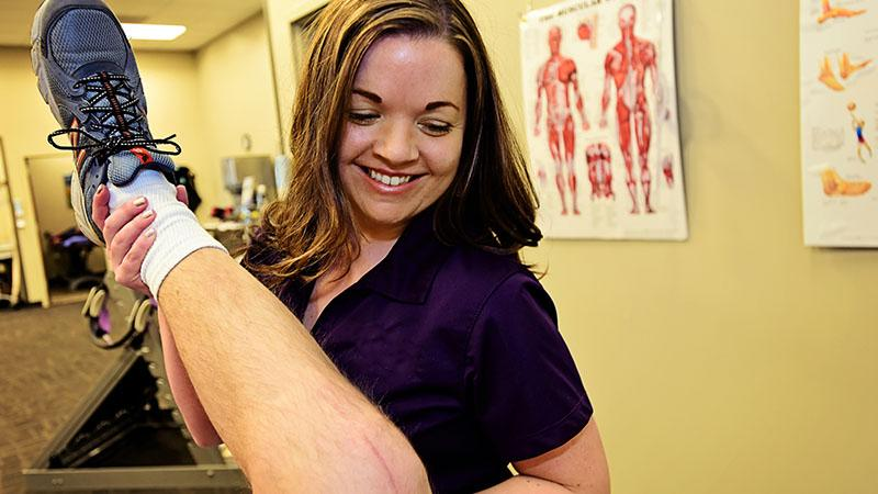 physical therapist with patient's leg