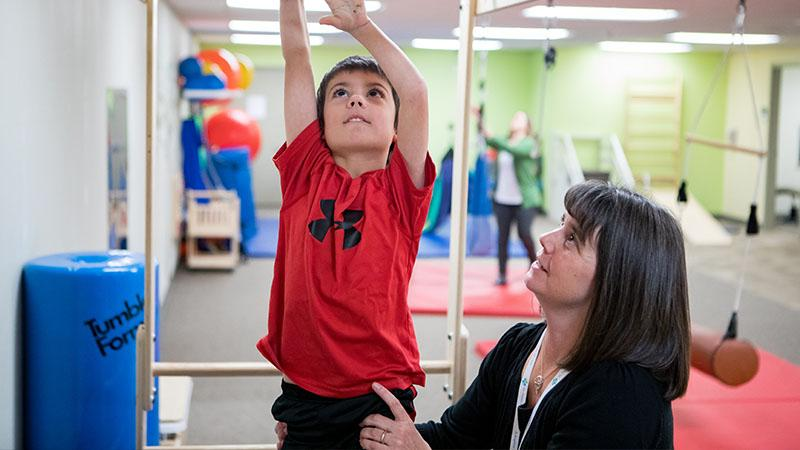 SPH pediatric therapist and patient on monkey bars